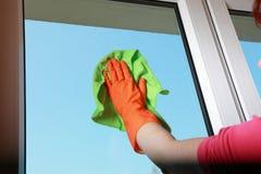 Ventana con guantes de la limpieza de la mano con el trapo Imágenes de archivo libres de regalías