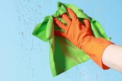 Ventana con guantes de la limpieza de la mano con el trapo Imagen de archivo