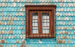 Ventana con la fachada del revestimiento de madera de madera de la turquesa, Chile imagenes de archivo