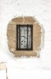 Ventana con las barras de metal y malla en la pared blanqueada Fotos de archivo