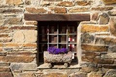 Ventana con las flores en el travesaño en un chalet de piedra Imagen de archivo