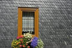 Ventana con las flores en una pared de la pizarra Imagenes de archivo