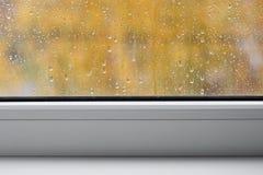 Ventana con las gotas de agua y los travesaños blancos, fondo del otoño Imagen de archivo libre de regalías