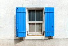 Ventana con los obturadores azules en el fondo blanco de la pared Fotografía de archivo