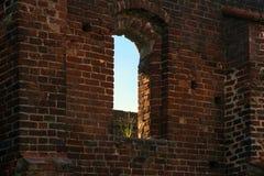 Ventana con un penacho de la hierba en una pared de ladrillo del rui del monasterio Fotos de archivo