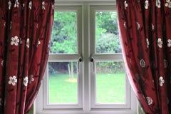 Ventana cubierta en cortinas Fotografía de archivo libre de regalías