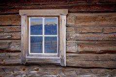 Ventana de cabaña de madera con la reflexión de la montaña Imagen de archivo