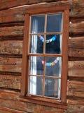 Ventana de cabaña de madera con las pequeñas banderas del rezo Foto de archivo libre de regalías
