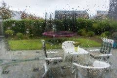 Ventana de cristal con las gotas de agua del agua que miran en el jardín con el fondo borroso del otoño del efecto foto de archivo