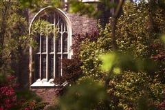 Ventana de cristal manchada de la iglesia a través de los árboles Fotos de archivo libres de regalías