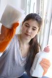 Ventana de la limpieza del adolescente en el vidrio de goma Imagen de archivo libre de regalías