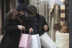 Ventana de los pares que hace compras al aire libre en invierno Fotos de archivo libres de regalías