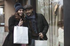 Ventana de los pares que hace compras al aire libre en invierno Imagen de archivo libre de regalías
