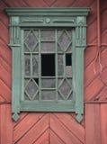 Ventana de madera adornada hermosa antigua verde en la pared roja Imagen de archivo