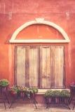 Ventana de madera de Toscana en la pared vieja anaranjada Fotografía de archivo libre de regalías