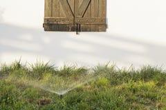 Ventana de madera rústica en una pared blanca detrás de la regadera de la hierba en la puesta del sol Fotos de archivo libres de regalías