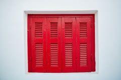 Ventana de madera roja en la pared blanca Foto de archivo