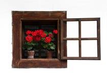 Ventana de madera tradicional abierta con las flores rojas Imagen de archivo libre de regalías