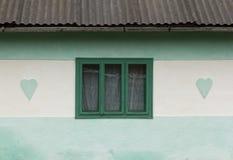 Ventana de madera verde enmarcada por dos adornos del corazón Imagen de archivo