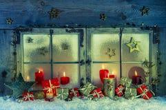 Ventana de madera vieja adornada para la Navidad con las velas y p rojos Fotografía de archivo