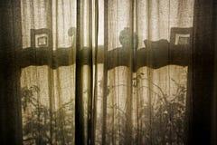 Ventana de marco vieja a través de las cortinas cerradas Imágenes de archivo libres de regalías