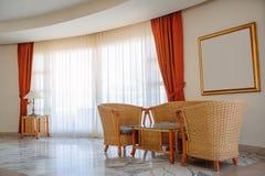 Ventana de mimbre de los muebles con las cortinas rojas Imagenes de archivo