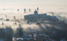 Ventana decorativa de una vivienda histórica lombardía El paisaje asombroso de la niebla sube de los llanos y cubre la ciudad vie fotografía de archivo