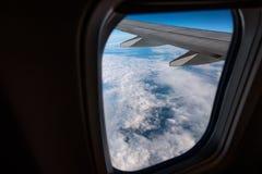 Ventana del aeroplano desde adentro A través de la ventana usted puede ver las nubes y el ala del aeroplano Foto de archivo