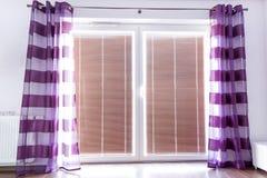 Ventana del balcón con las cortinas púrpuras imagenes de archivo