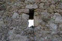 Ventana del castillo en la pared de piedra Fotografía de archivo libre de regalías