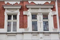 Ventana del diseñador de tres vintages en la fachada del hou viejo del ladrillo imagenes de archivo