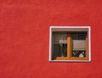 Ventana del marco de madera de Brown en la pared roja vibrante de la casa foto de archivo
