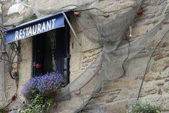 Ventana del restaurante de los mariscos con las flores y la red foto de archivo
