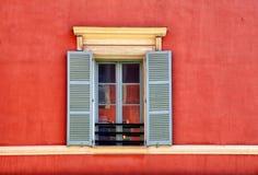 Ventana del vintage con los obturadores grises en la casa roja vieja del estuco, Niza, Imágenes de archivo libres de regalías