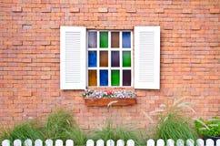 Ventana del vintage con los obturadores que se abren y las flores frescas con el vidrio y la pared de ladrillo coloreados imagenes de archivo