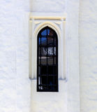 Ventana en la pared blanca del monasterio con la reflexión la cara el reloj Foto de archivo libre de regalías