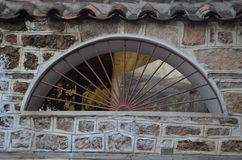 Ventana en la pared de piedra con la reja Imagen de archivo libre de regalías
