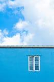 Ventana en pared azul Fotos de archivo