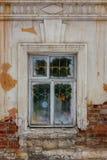 Ventana en una casa vieja, paredes de ladrillo con yeso que desmenuza Fotografía de archivo libre de regalías