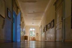 Ventana grande en el final de un vestíbulo en casa colonial abandonada foto de archivo