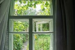 Ventana gris vieja con las cortinas en el cuarto en un día de verano brillante fotos de archivo libres de regalías
