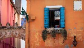 Ventana italiana azul brillante con la jaula amarilla que cuelga en ella foto de archivo