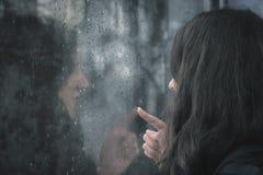 Ventana lluviosa conmovedora de la mujer joven fotos de archivo libres de regalías