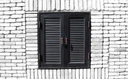 Ventana negra vieja en el fondo blanco de la pared de ladrillo Fotos de archivo libres de regalías