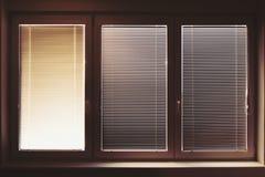 Ventana plástica cerrada el día soleado con las persianas plásticas horizontales fotografía de archivo