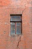 Ventana quebrada en la pared roja Imagenes de archivo