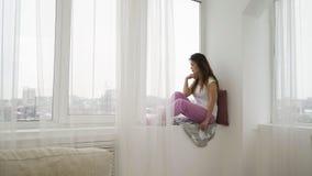 Ventana relajante de la muchacha del ocio de la soledad de la soledad Foto de archivo libre de regalías