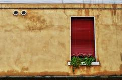 Ventana roja en una pared bronceada Fotos de archivo