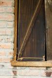 Ventana Shuttered de madera rústica de un establo del ladrillo Foto de archivo