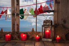 Ventana-travesaño adornado con las velas rojas de la Navidad: opinión a Oc Imagen de archivo libre de regalías